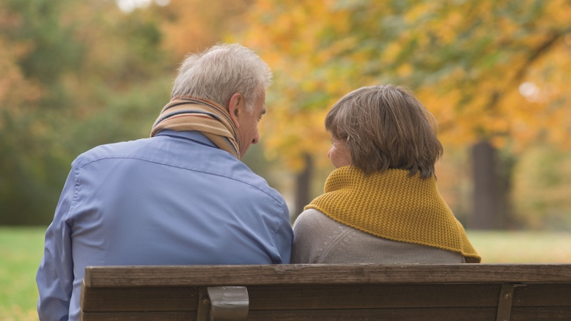 An elderly couple are sat on a bench looking at each other